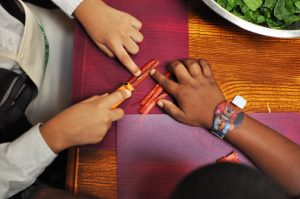 Crispus Attucks students learning knife skills by slicing red peppers.