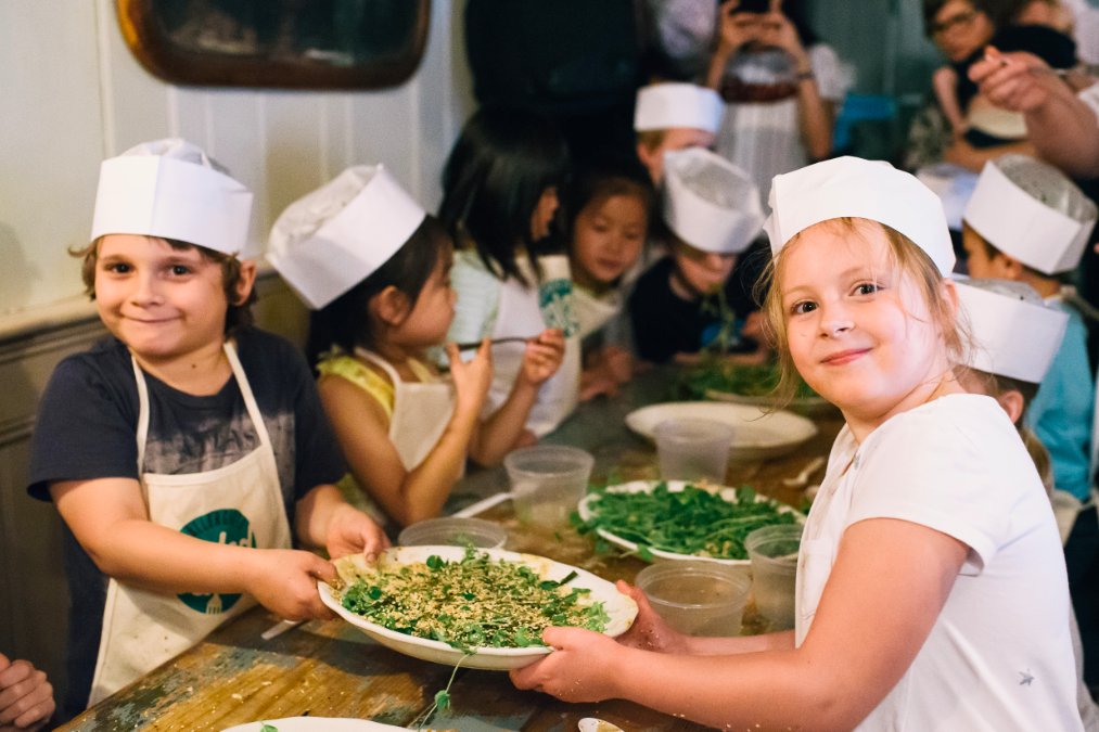 little chefs holding up a plate of spring peas during an Allergic to Salad Cooking Class